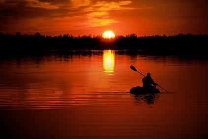 man in kayaking on Lake at sunset